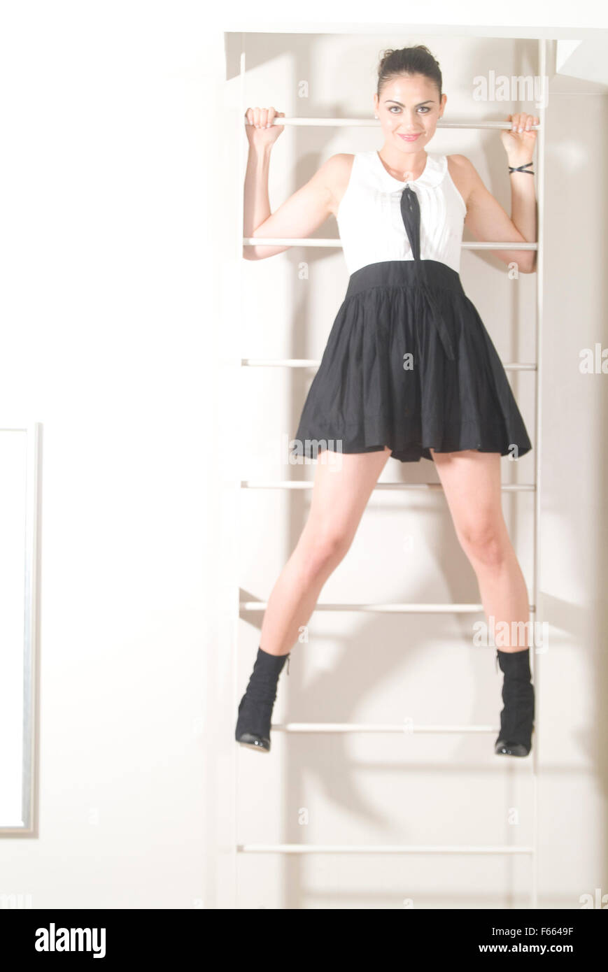 Girl in a black and white school girl dress climbing a latter facing the camera.  Caught in the moment on camera. - Stock Image