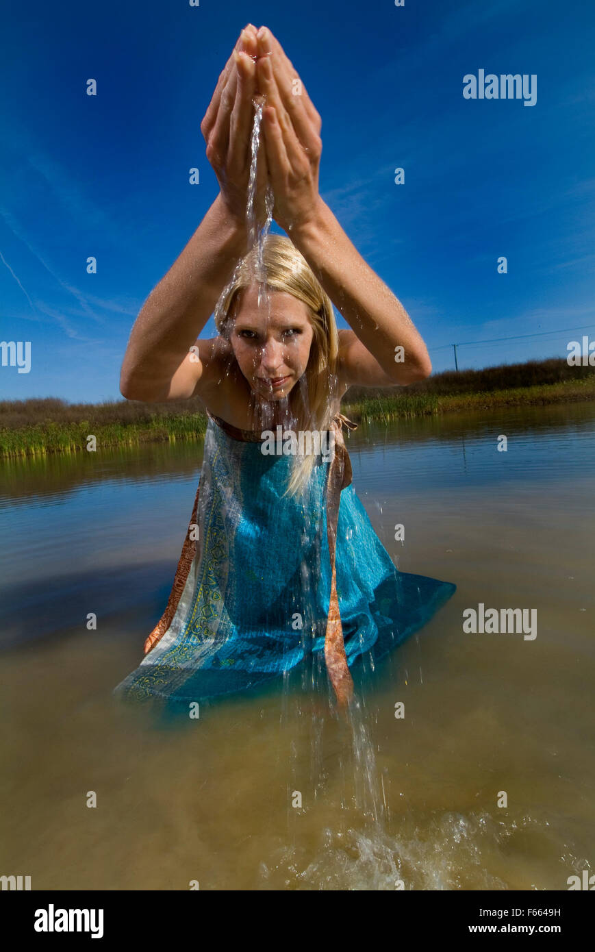 A blond haired woman in water outdoors lifting water up and out of her hands. Abundance concept, great blue skies, - Stock Image