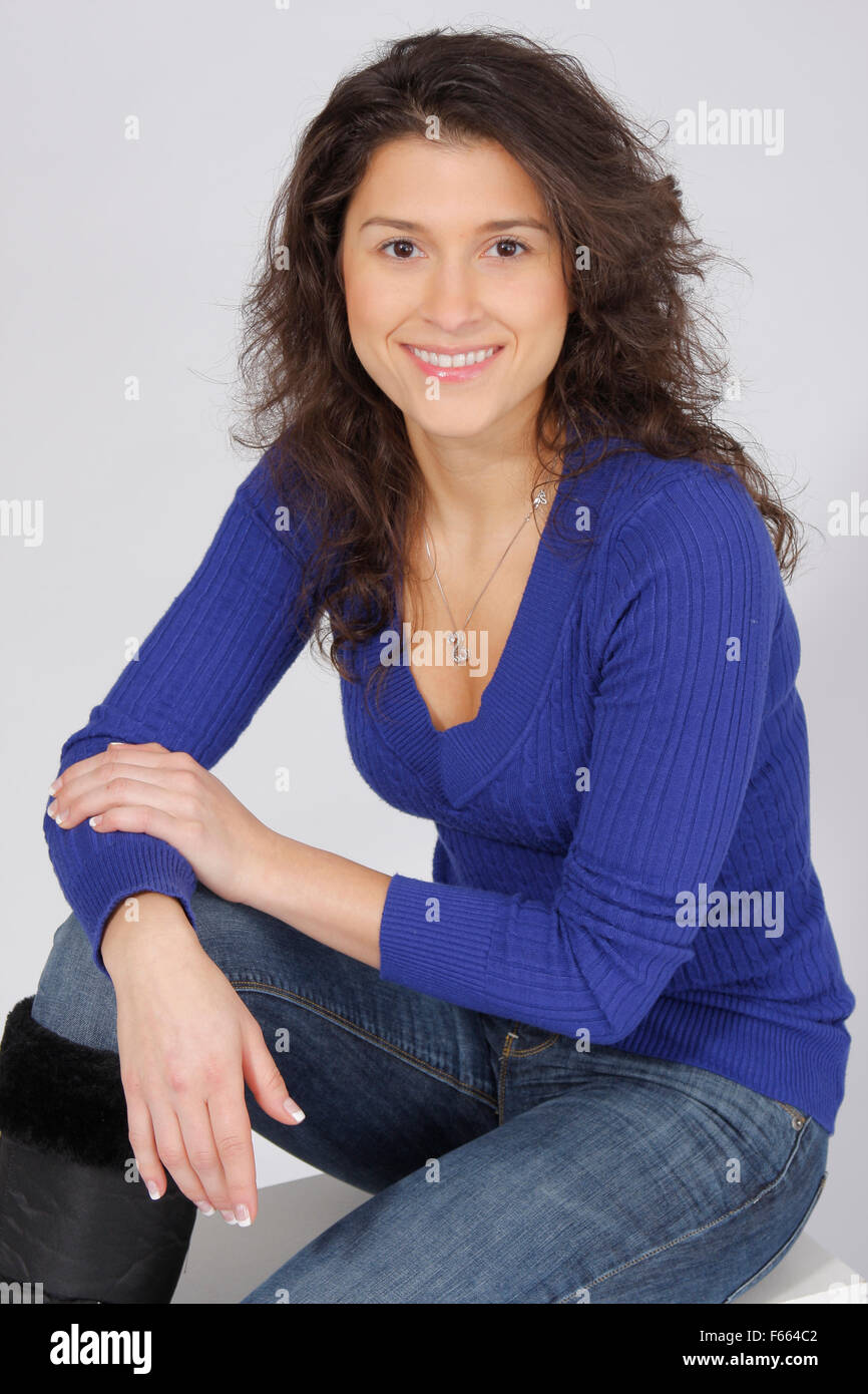 Portrait of a brunette female sitting wearing a blue sweater on a white block and sweep. - Stock Image