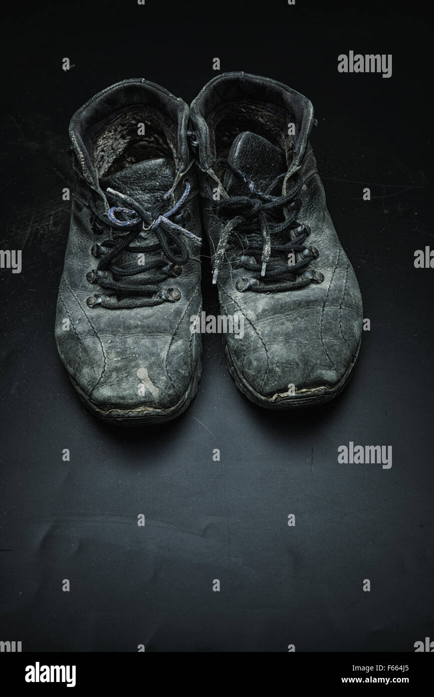 Old black worn out shoes on the black floor - Stock Image