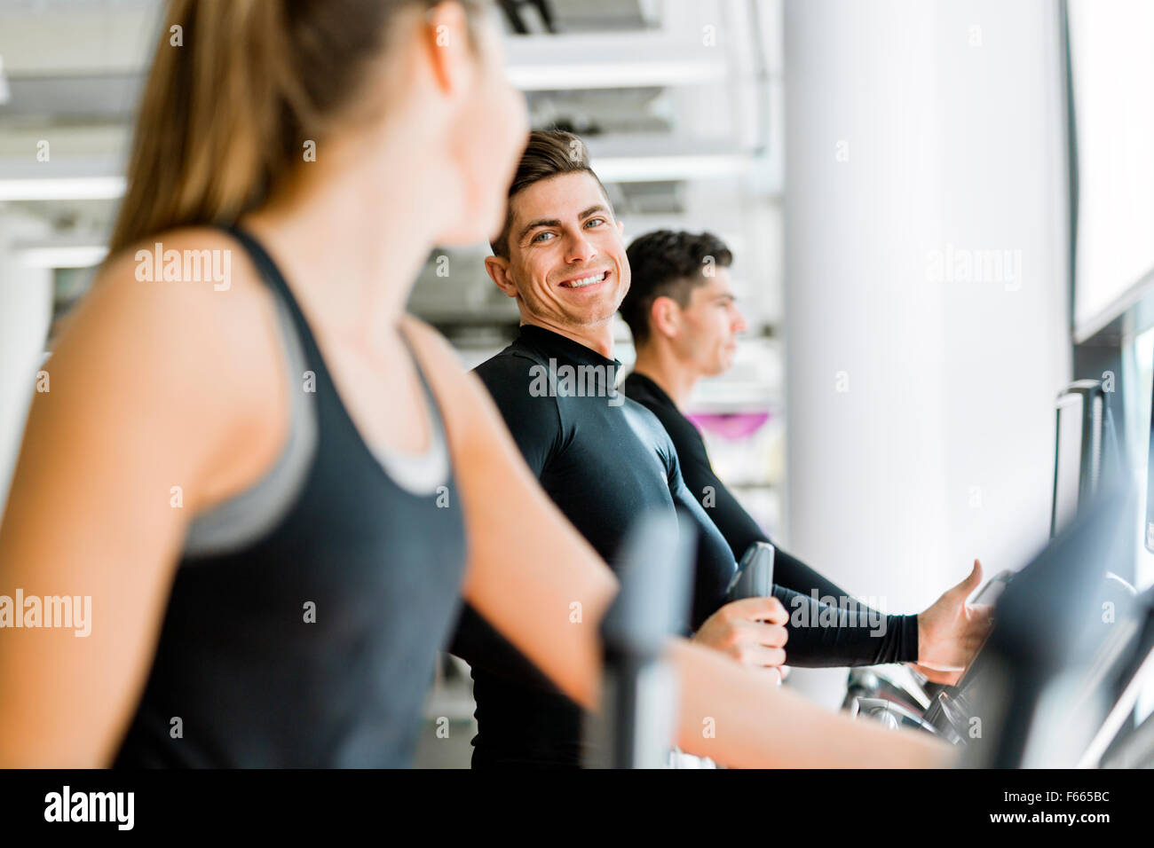 Handsome man and beautiful young woman using a stepper in a gym and having a conversation - Stock Image