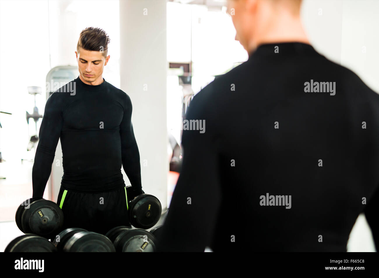 Young muscular man working out in a gym and lifting weights with his reflection showing in a mirror - Stock Image