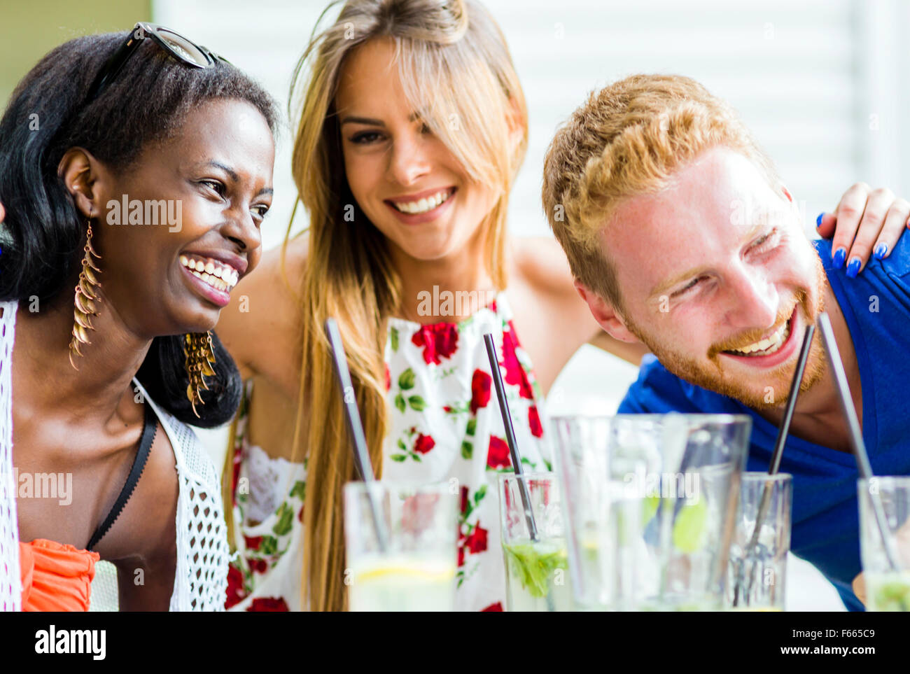 Friends laughing and hugging each other outdoors and being happy - Stock Image