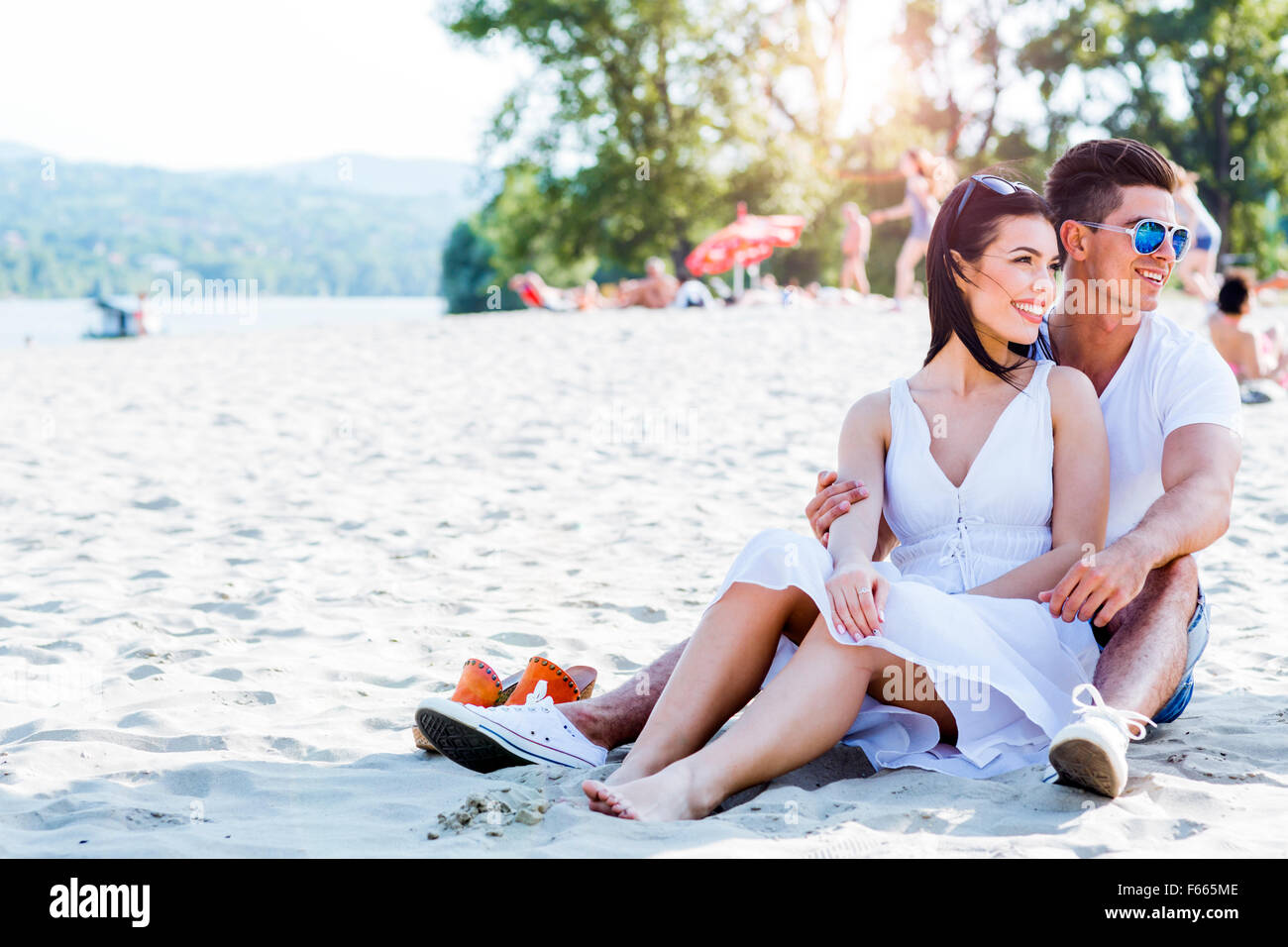 Romantic young couple in love sitting at a sandy beach and smiling - Stock Image