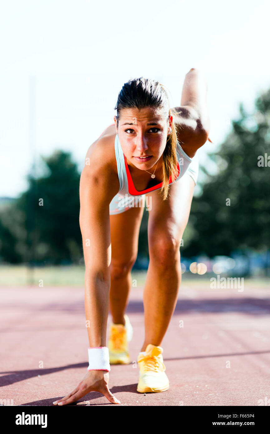 Beautiful female sprinter getting ready for the run during summer - Stock Image