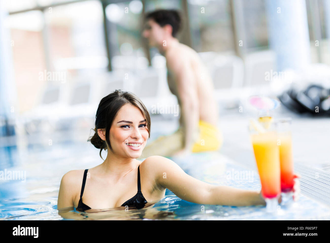 Couple drinking a cocktail by the swimming pool and relaxing - Stock Image