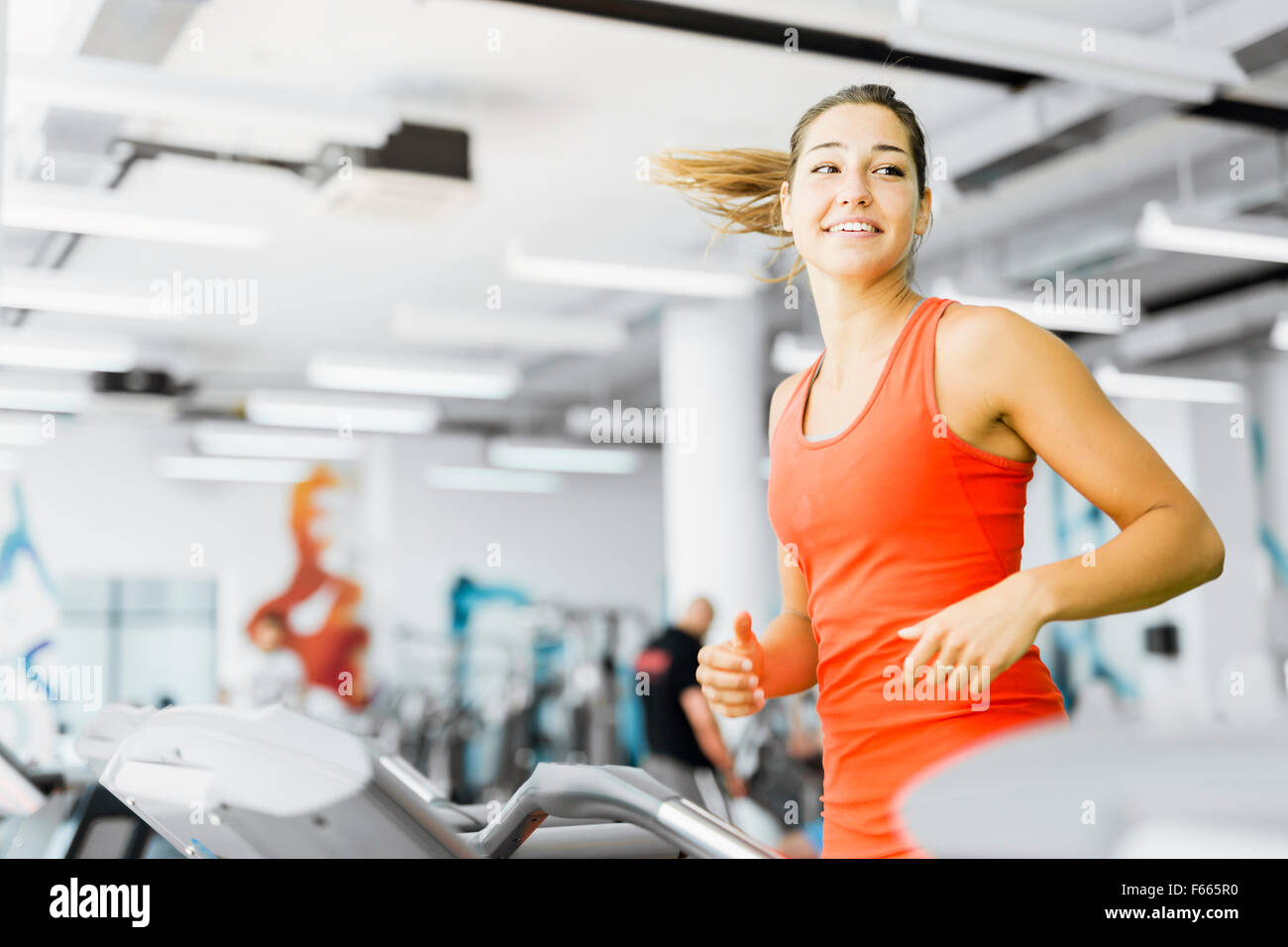 Beautiful young woman running on a treadmill in gym and smiling - Stock Image