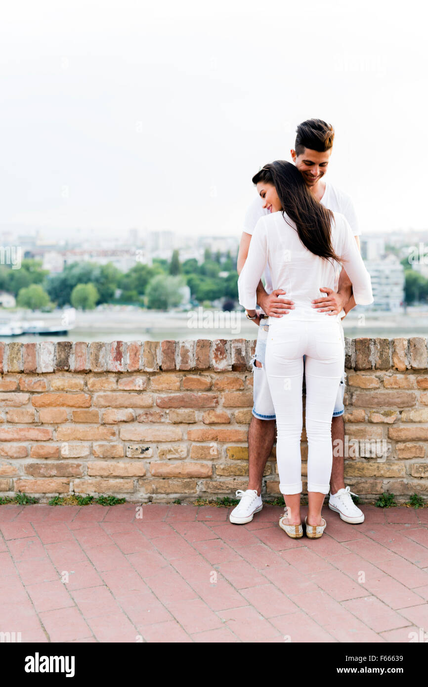 Young couple holding each other around waist and being close to each other - Stock Image