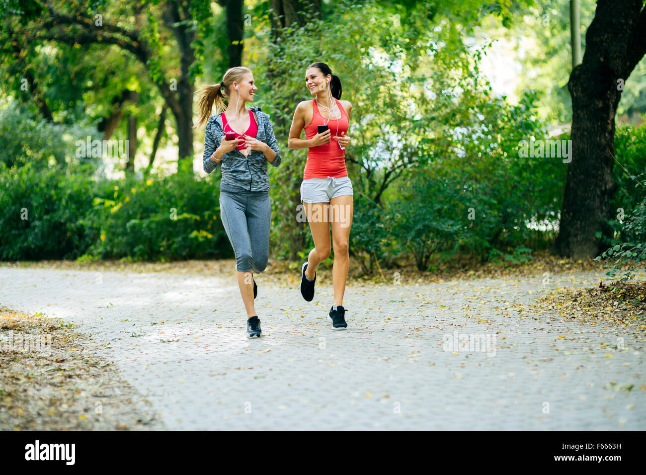 Energetic young women running outdoors in park to keep their bodies in shape - Stock Image