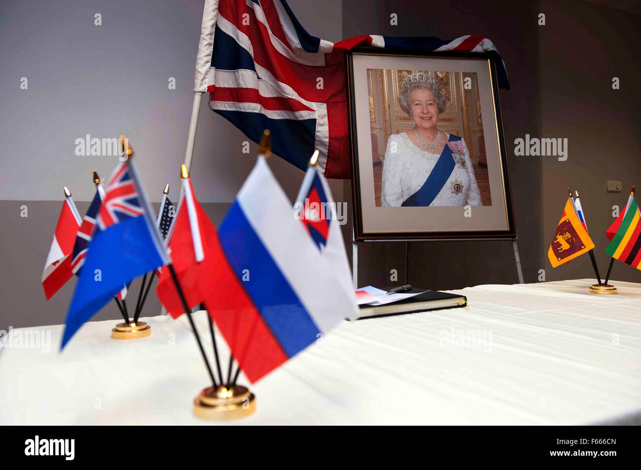 A portrait of the Queen of England on a table adorned with the Union Jack and Common Wealth flags during a Citizenship - Stock Image