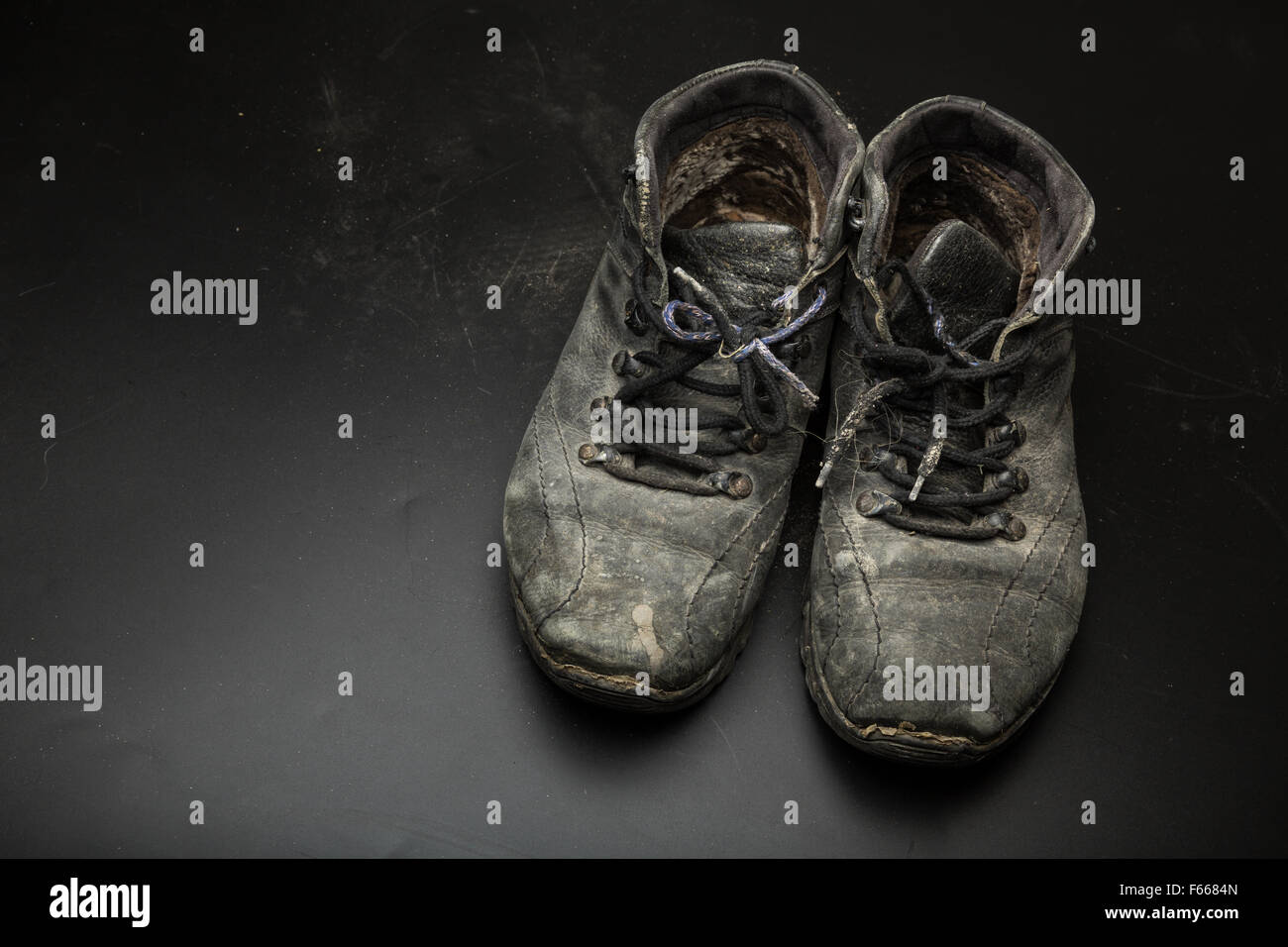 Old worn out shoes on the floor - Stock Image