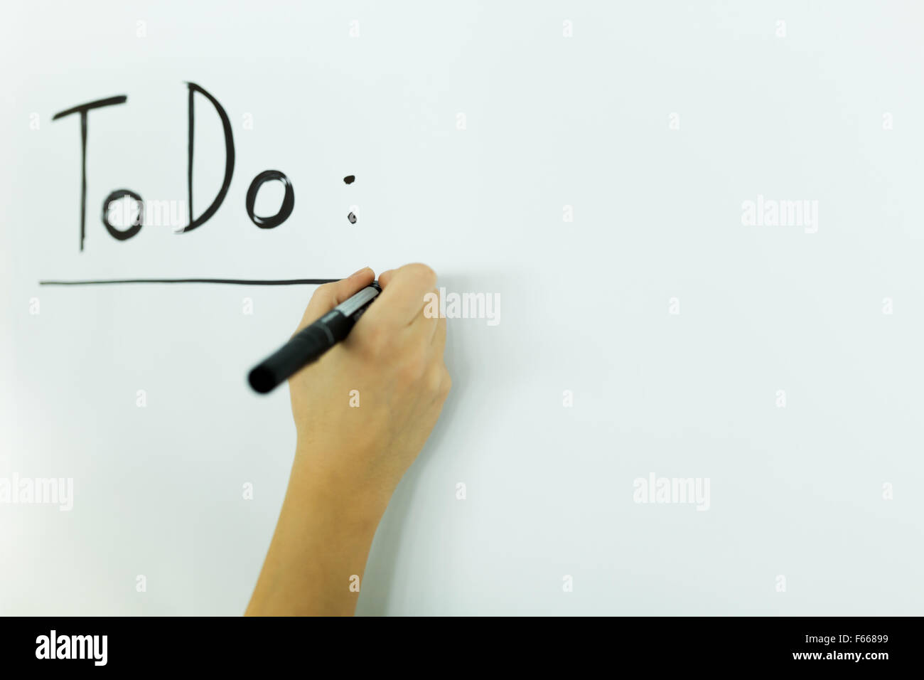 writing todo onto a white writing board - Stock Image