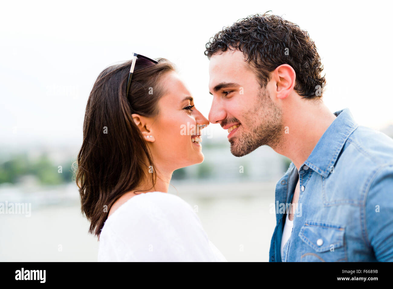 Young beautiful couple rubbing noses as a sign of love and about to kiss each other - Stock Image