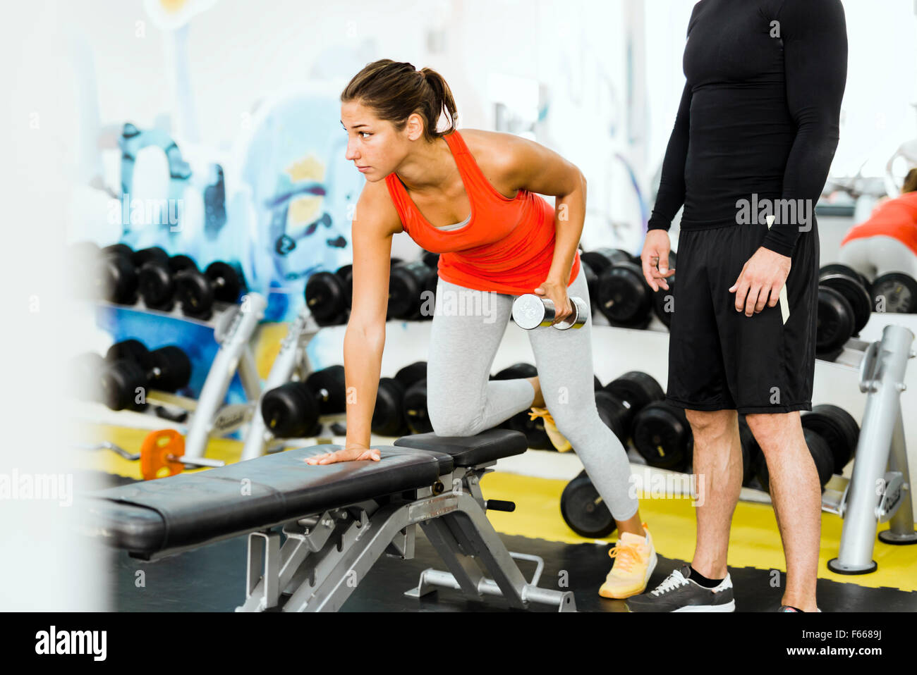 Young male trainer giving instructions to a woman in a gym and being supportive - Stock Image