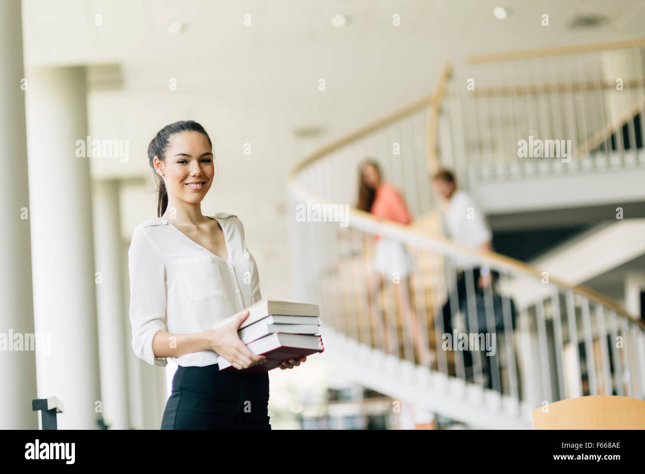 Beautiful woman holding books and smiling in a modern library - Stock Image