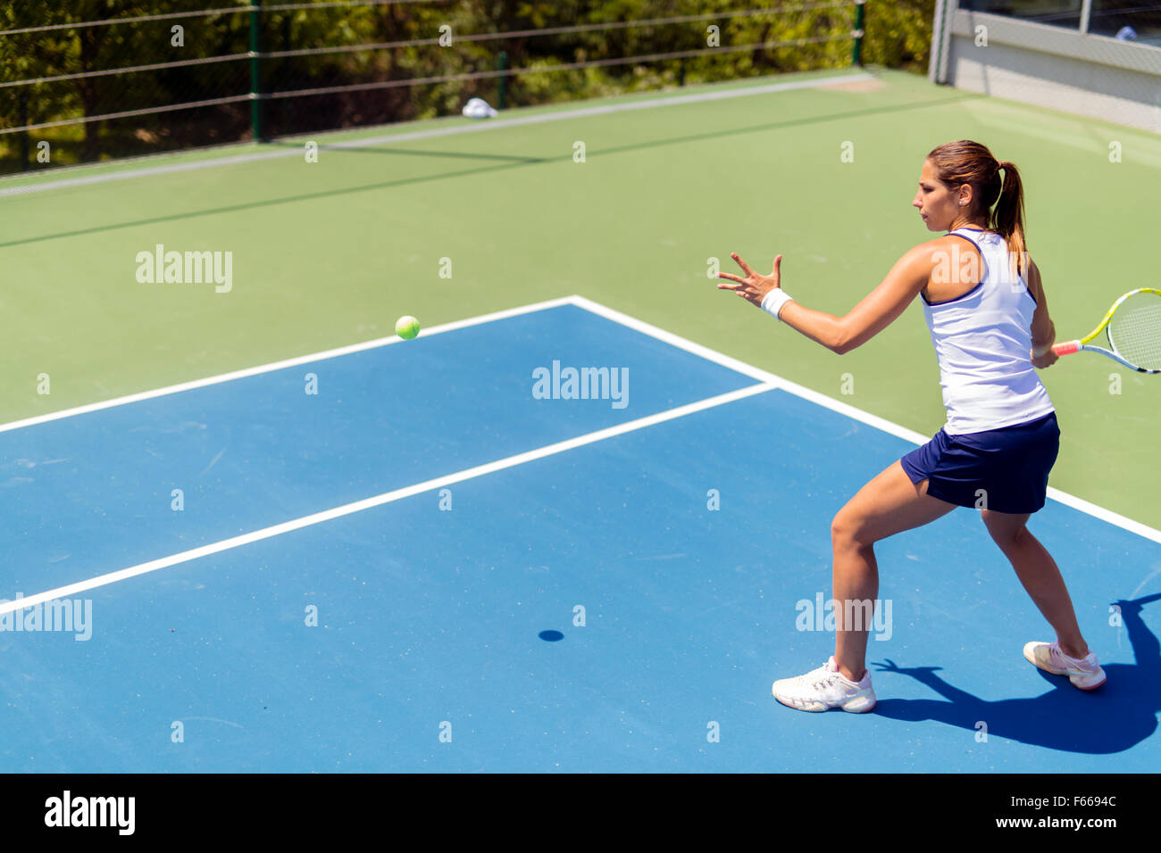 Beautiful female tennis player in action, hitting a forehand - Stock Image