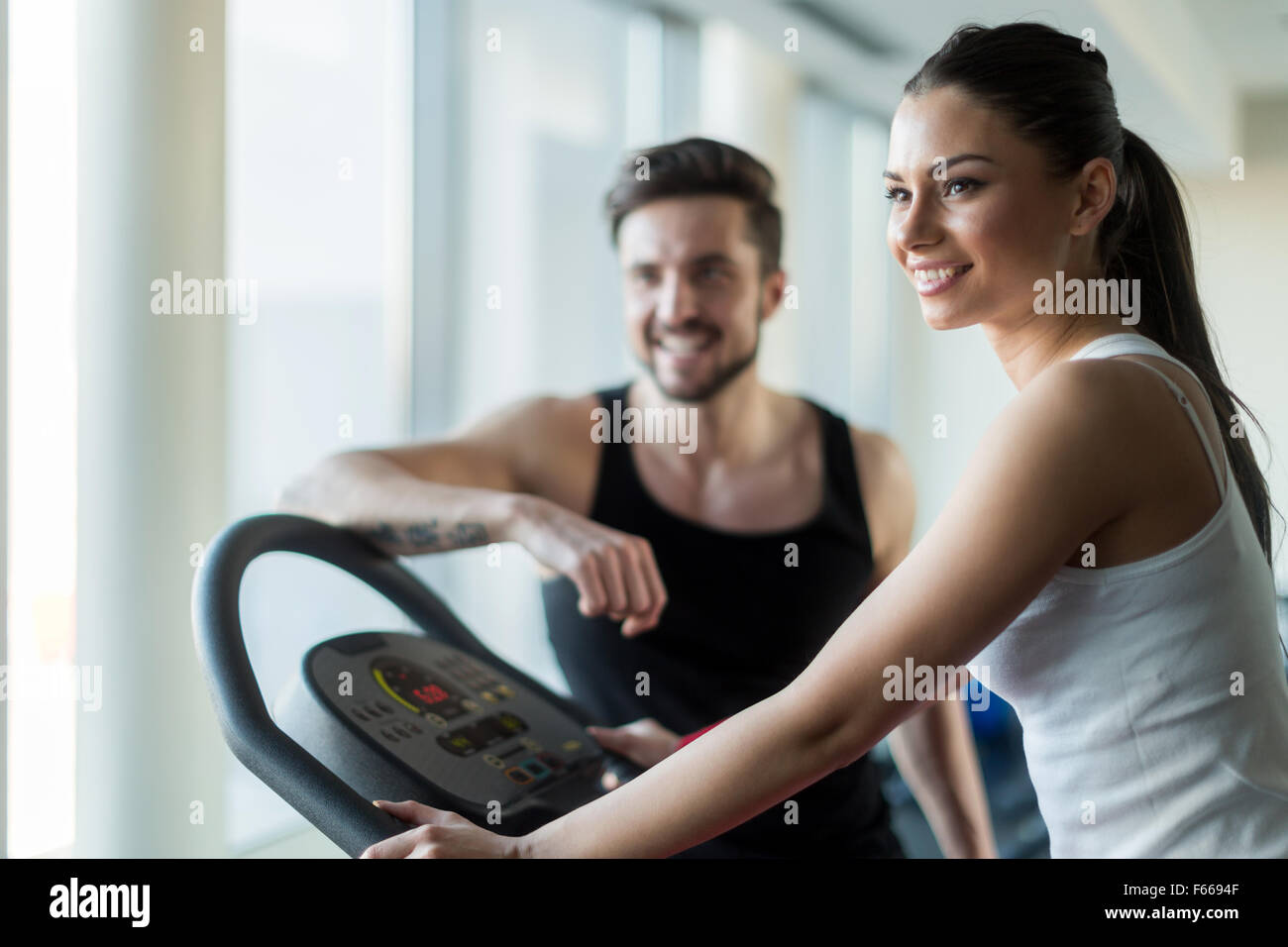 Beautiful, young people talking in a gym while working out and burning calories Stock Photo