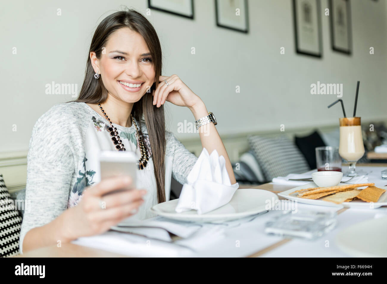 Beautiful smiling lady sitting in a restaurant at a table and holding her cell phone - Stock Image