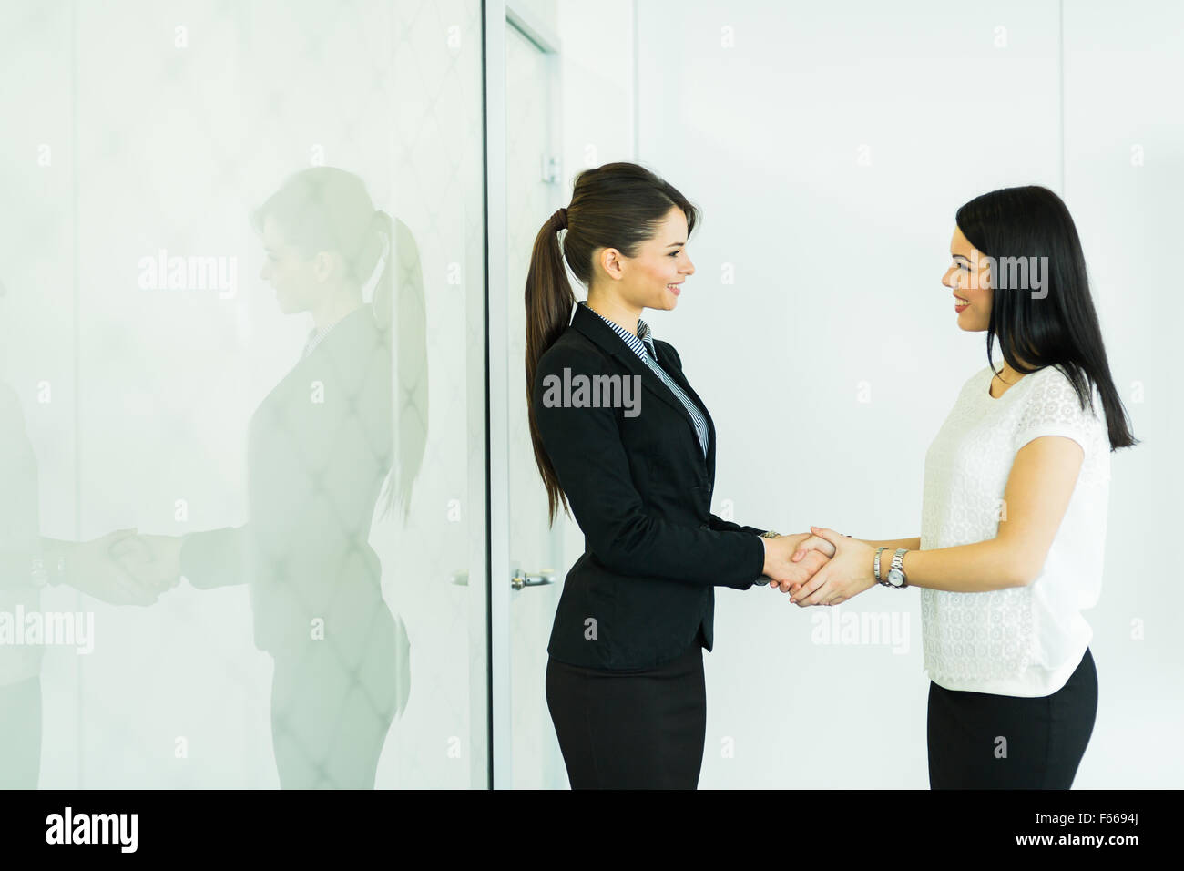 Handshake between two colleagues in a business office - Stock Image