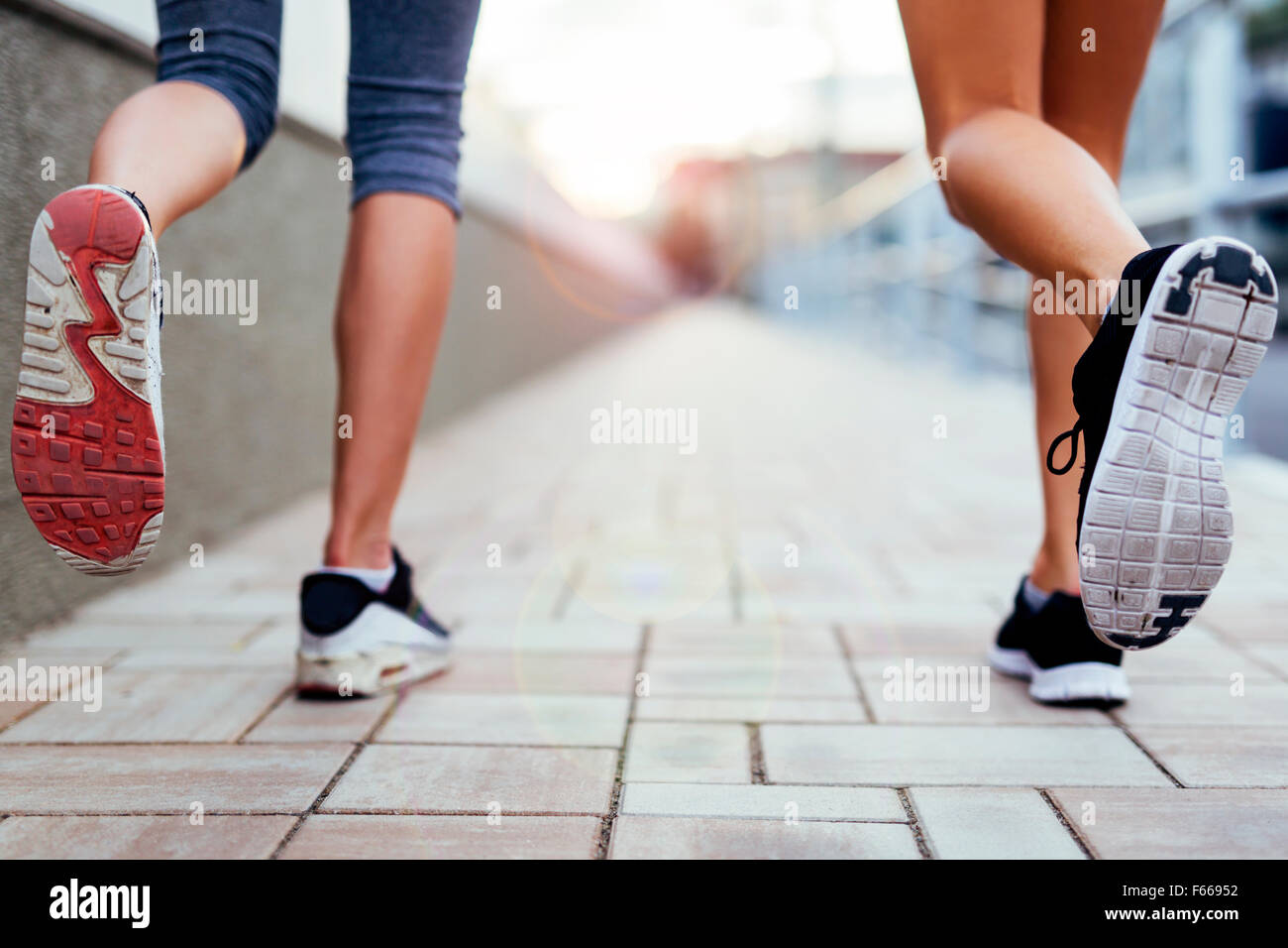 Closeup of joggers' feet and shoes while in motion - Stock Image