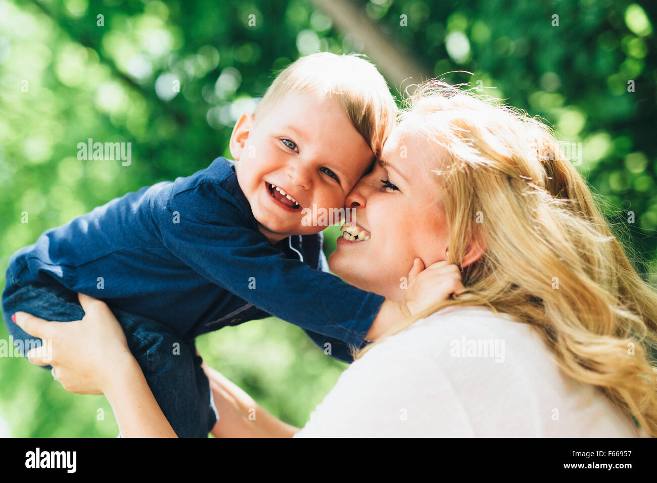 Mother smiling laughing and playing with her child outdoors on a nice summer day - Stock Image