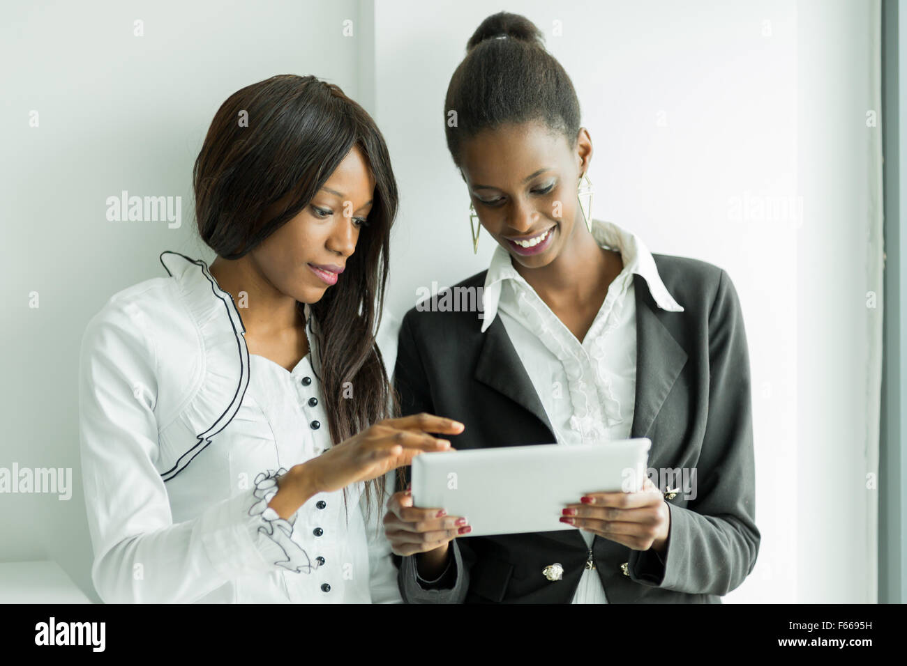 Two colleagues talking while standing about the contents on a tablet pc in a well lit office close to the window Stock Photo