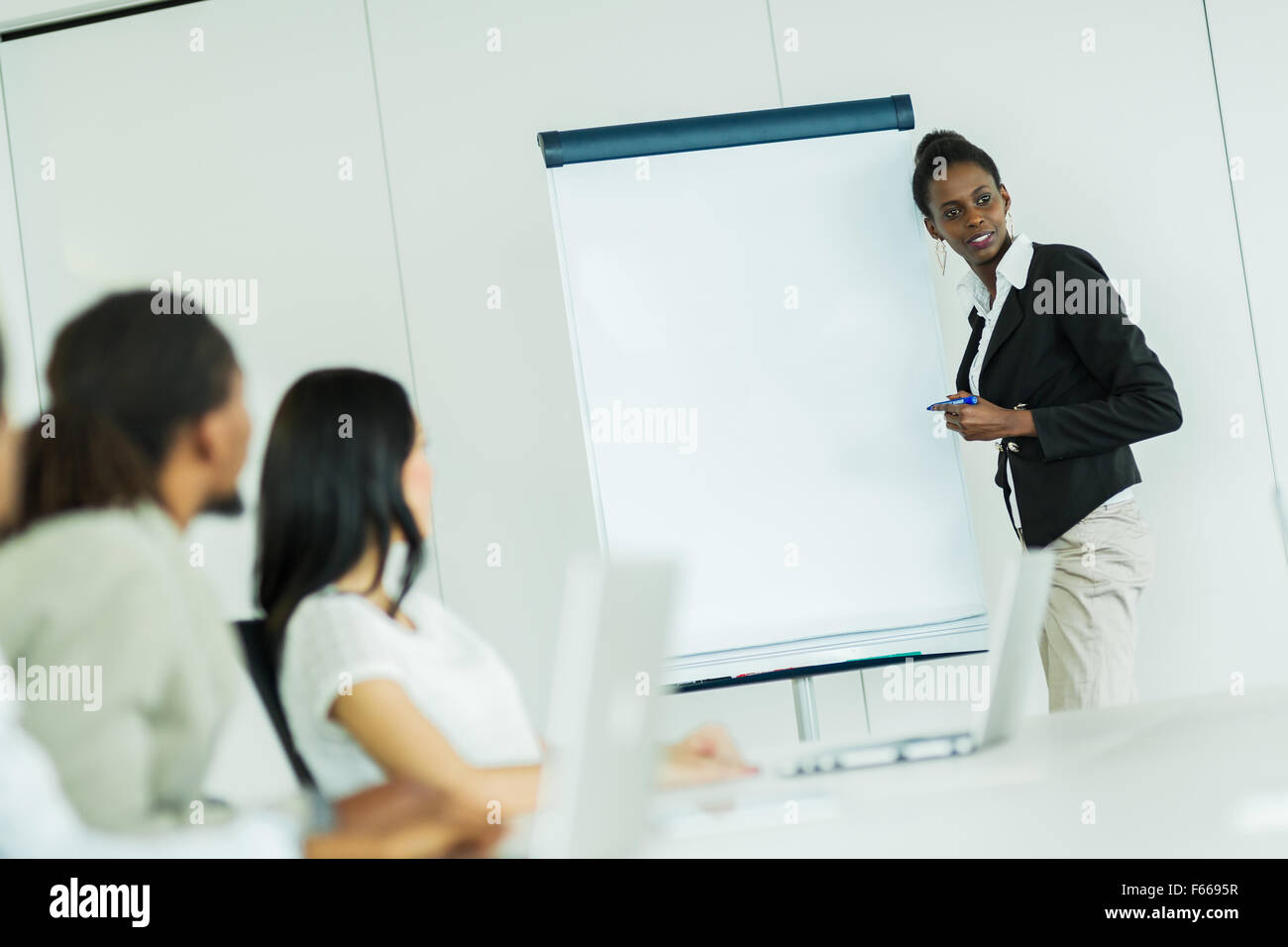 Young business people sitting at a conference table while listening to their  colleague and learning new technologies - Stock Image