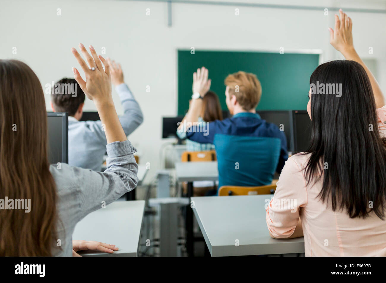Young students raising hands in a classroom showing they are ready - Stock Image