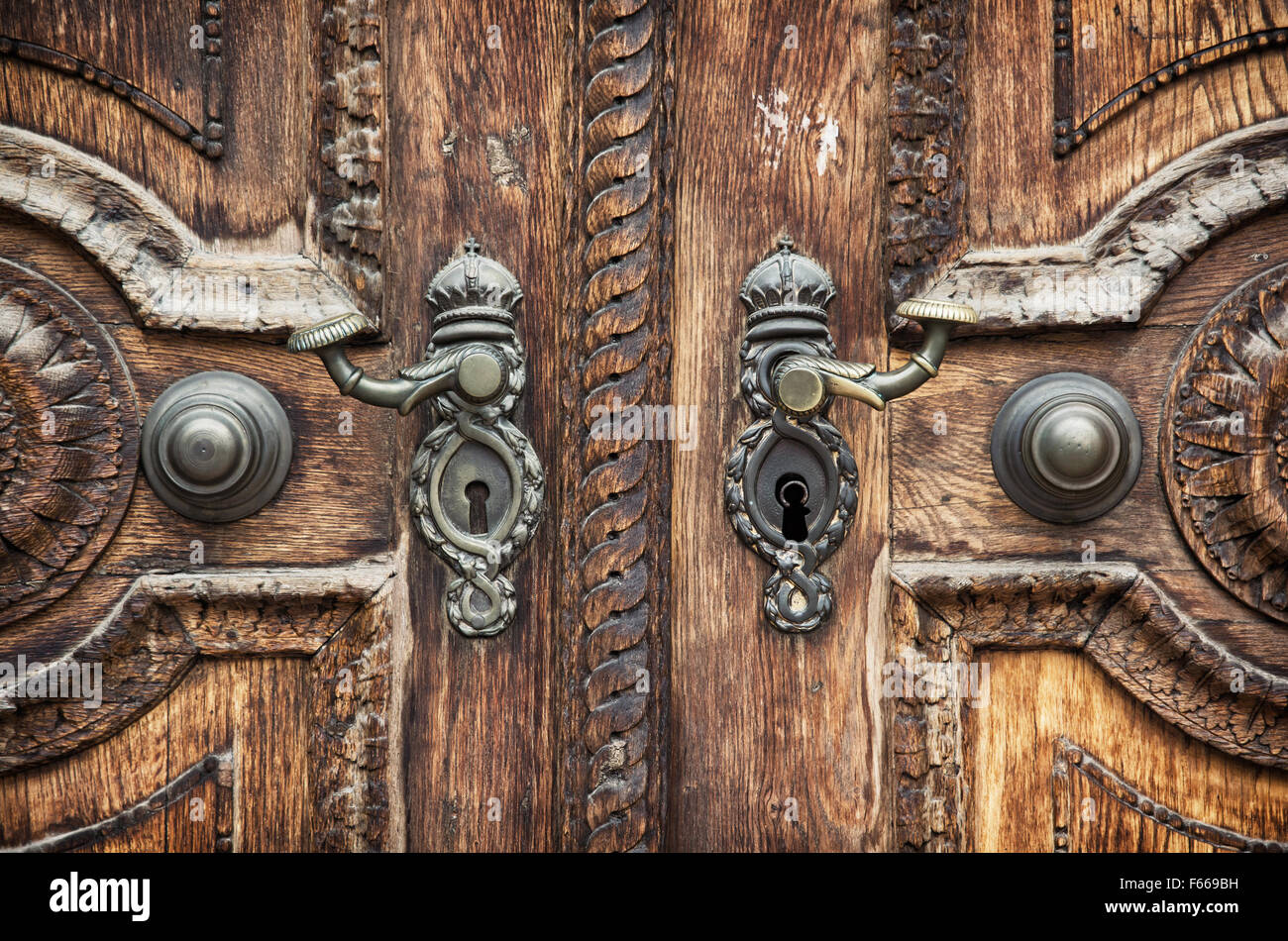 Old Hand Carved Wooden Pattern On The Door With Forged Crank.   Stock Image