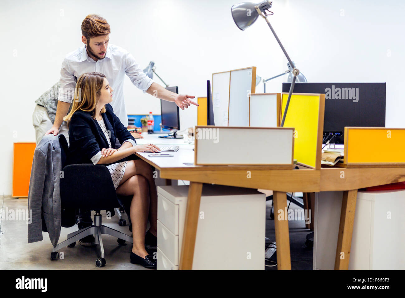 Business people in office working on a computer - Stock Image