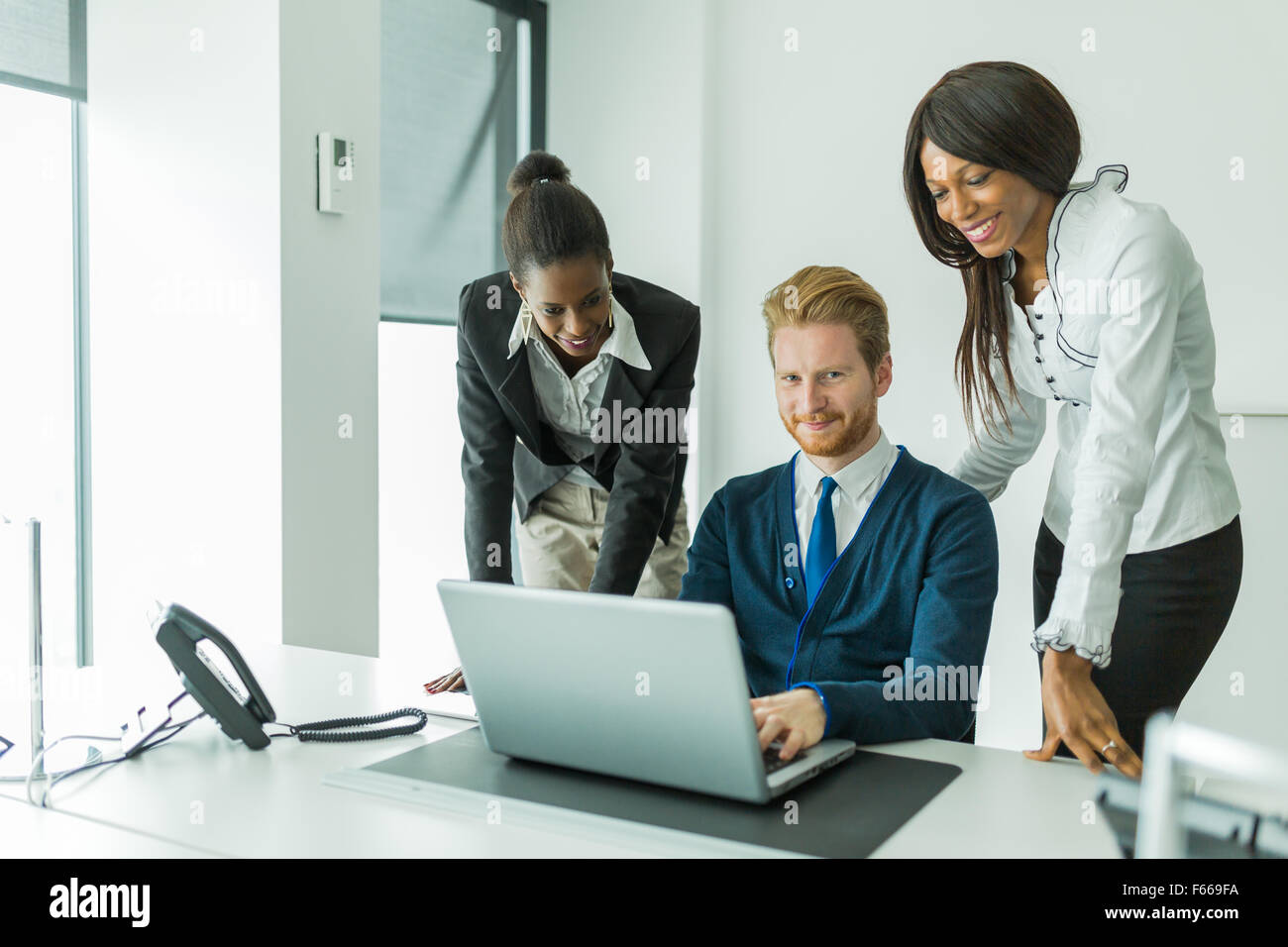 Business people talking and smiling in an office in front of a notebook - Stock Image