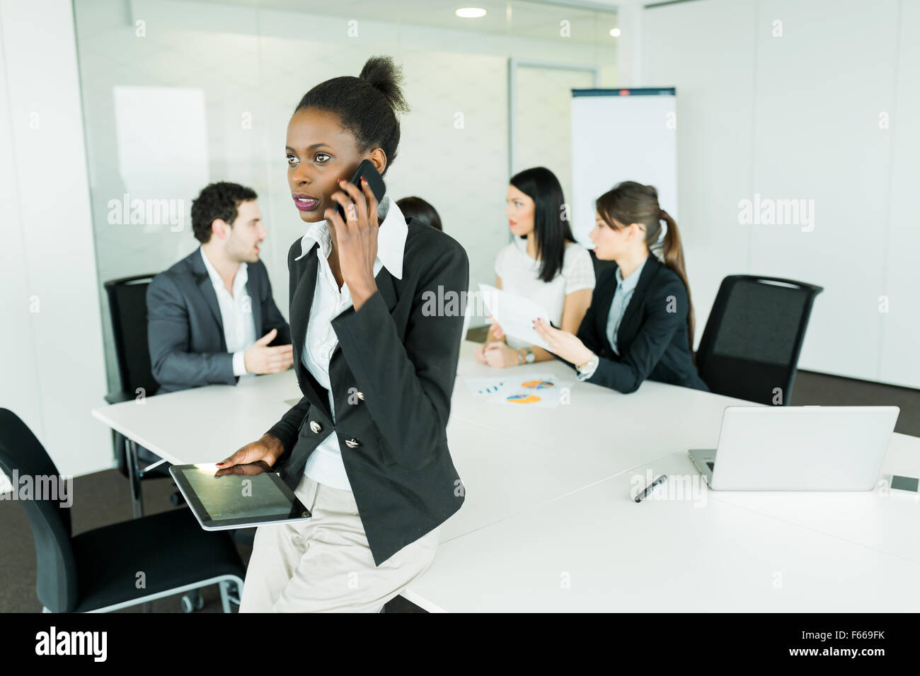 Beautiful, young, black businesswoman holding a tablet at an office meeting and getting bad news on the phone which - Stock Image