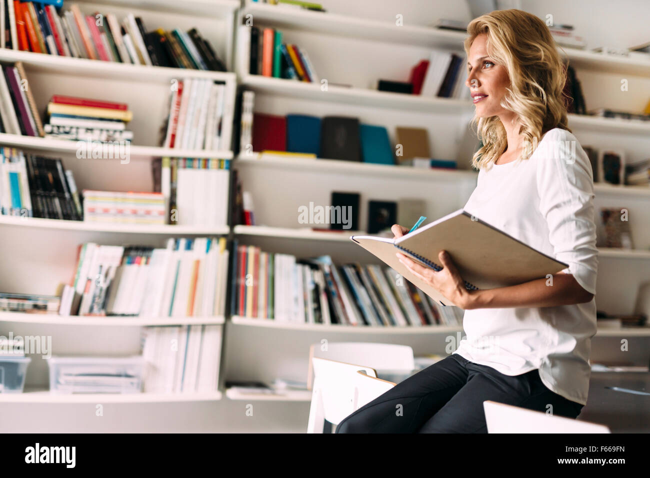 Stunning blonde woman reading - Stock Image