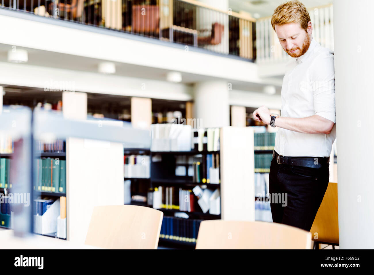 Handsome student checking time in library and smiling - Stock Image