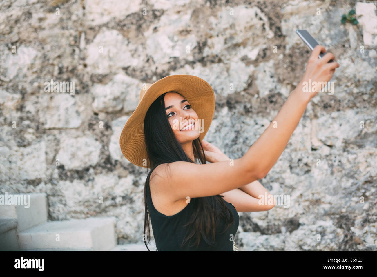 Beautiful girl taking a selfie and having a good time during summer - Stock Image