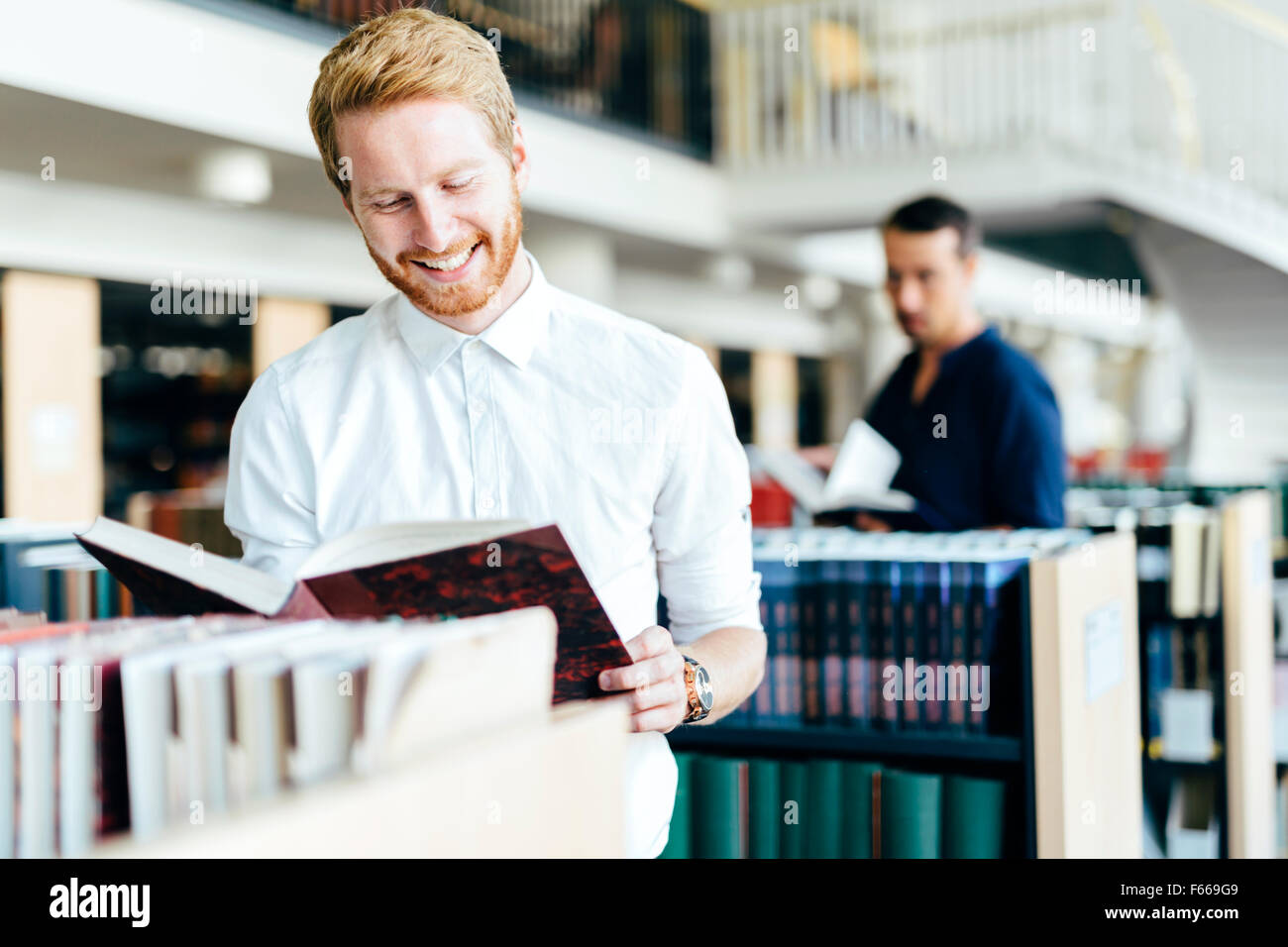 Handsome student reading a book in a beautiful library - Stock Image
