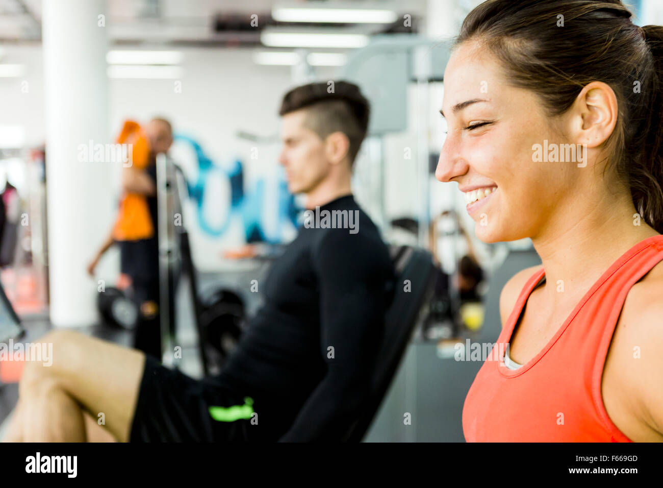 A handsome man and a beautiful woman working out together in a gym and bonding - Stock Image