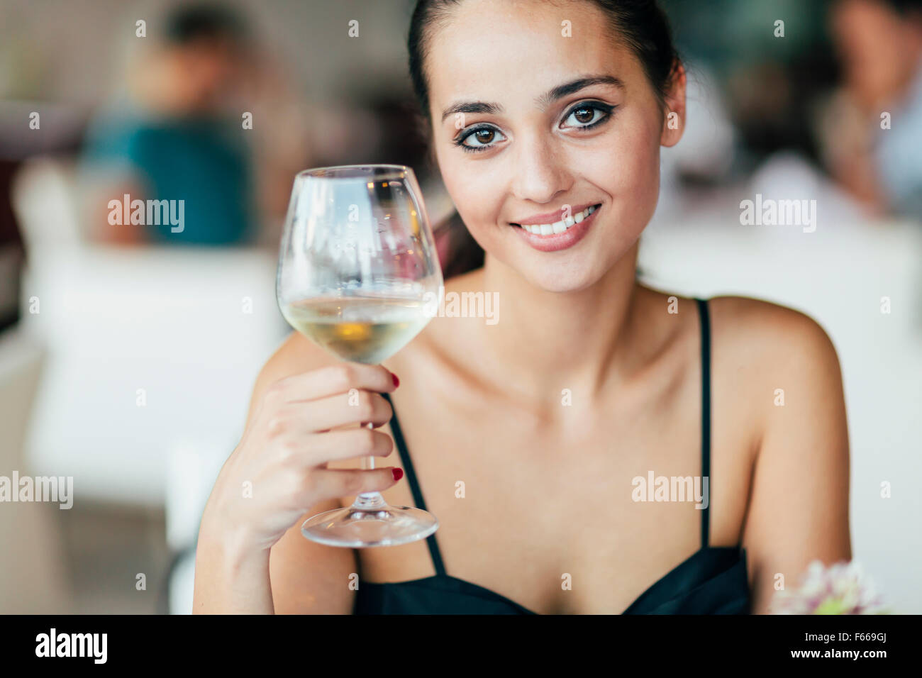 Woman tasting white wine in restaurant and lifting glass accordingly - Stock Image