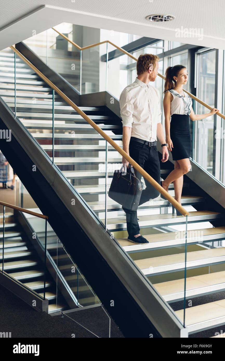 Businessman and businesswoman walking and taking stairs in a modern office building - Stock Image