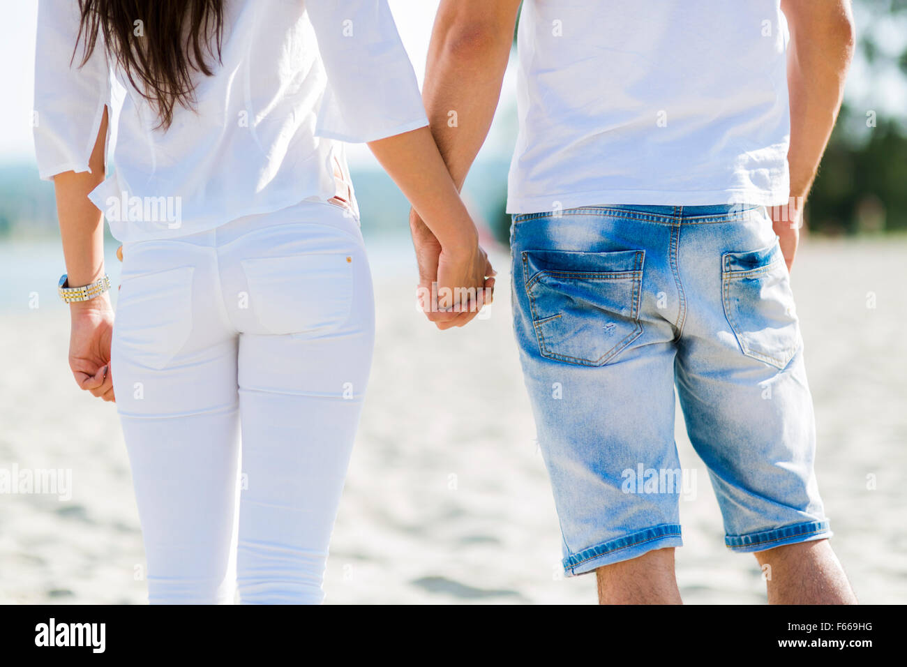 Romantic couple holding hands on a beach - Stock Image