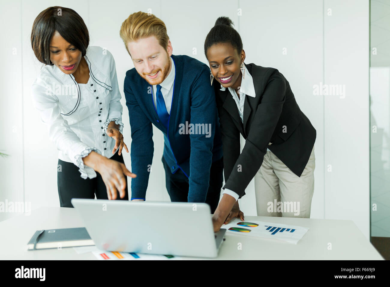 Business brainstorming by happy, nicely dressed multi-ethnic people in a clean, white office - Stock Image