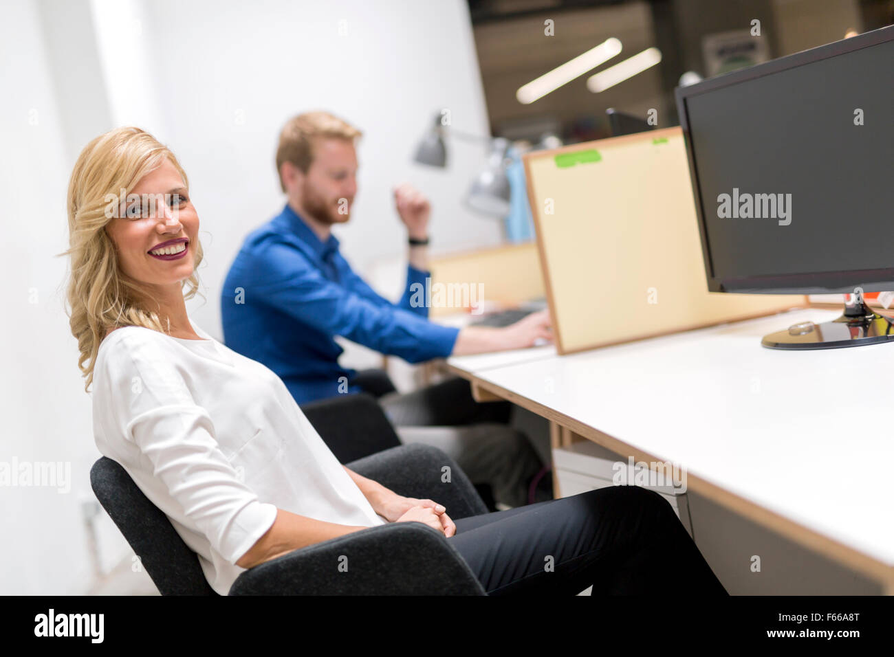 Beautiful blonde sitting in an office and working Stock Photo