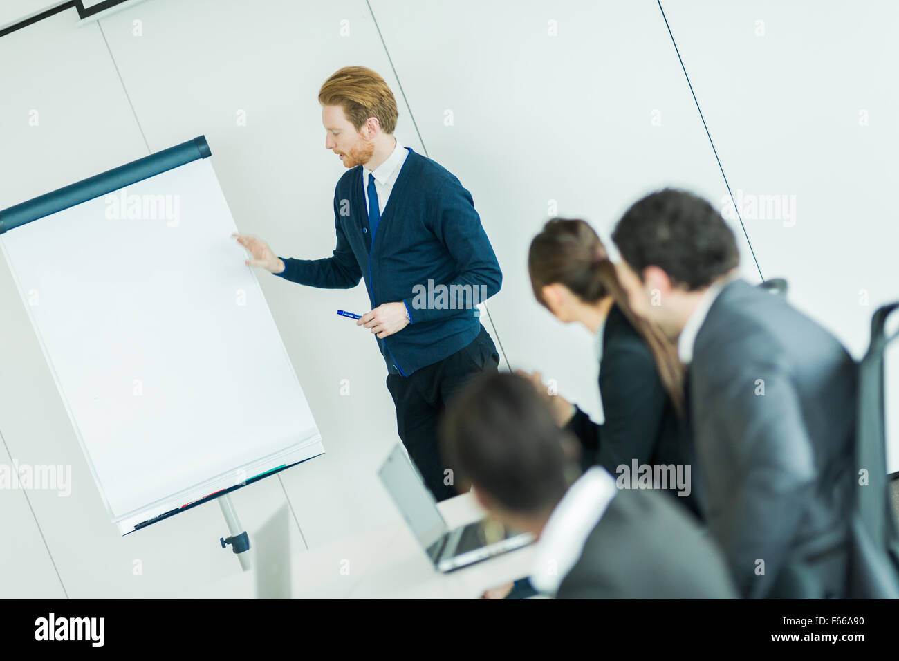 Young business people sitting at a conference table while listening to the lecturer  and learning new technologies - Stock Image
