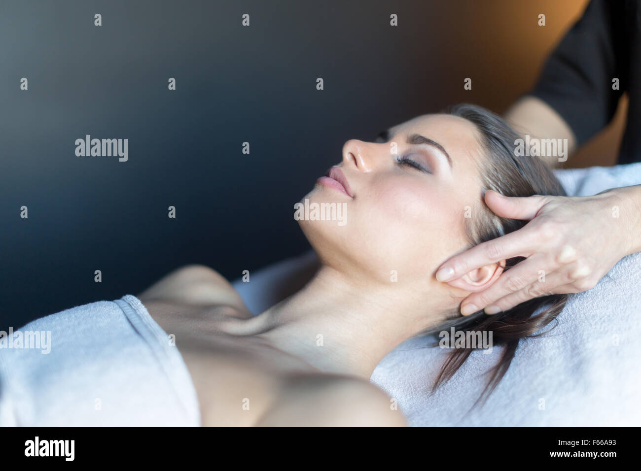 Masseur treating face of a beautiful, young woman lying on the massage table Stock Photo