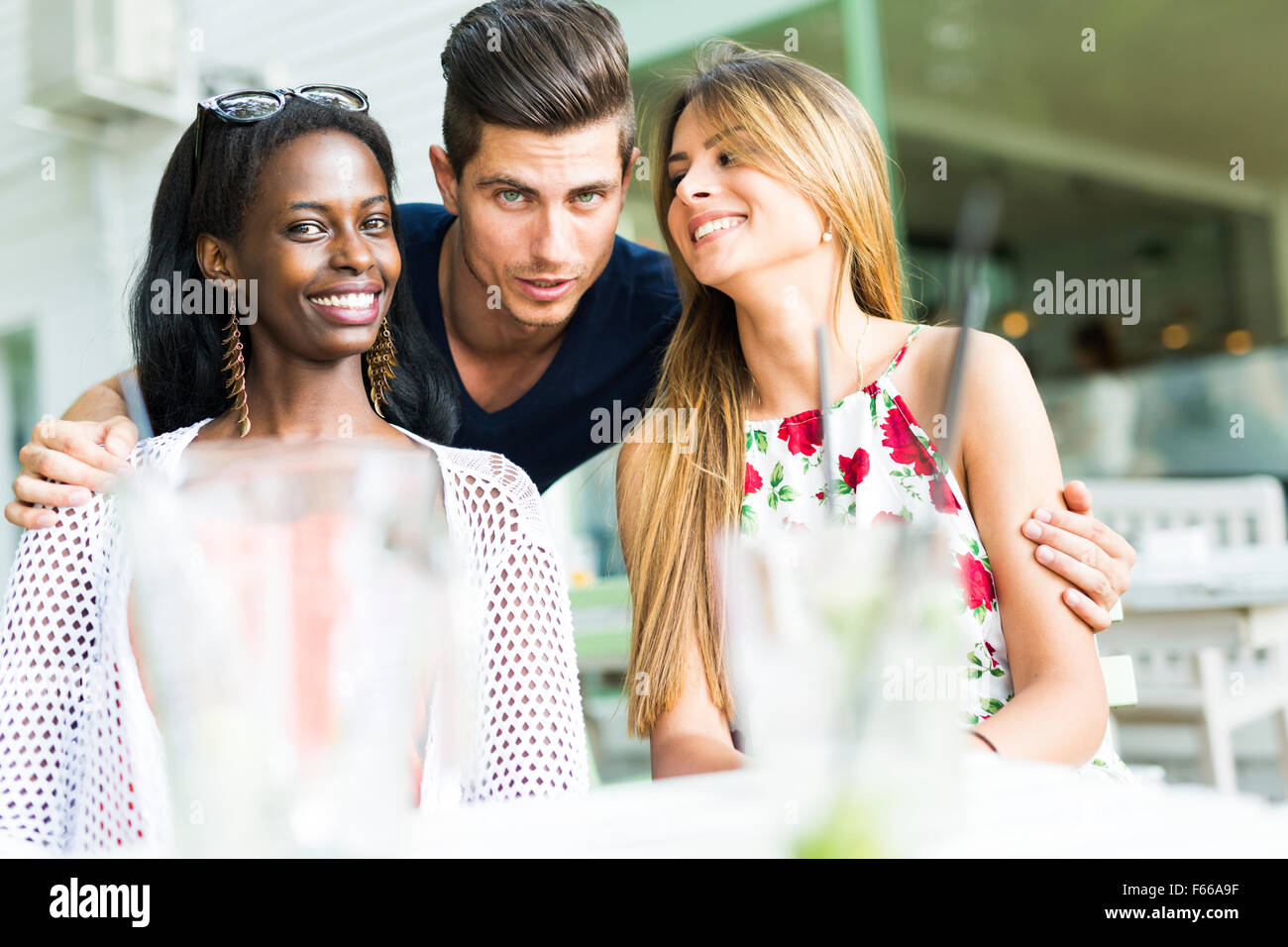 Happy young friends smiling outdoors being close to each other on a summer day - Stock Image