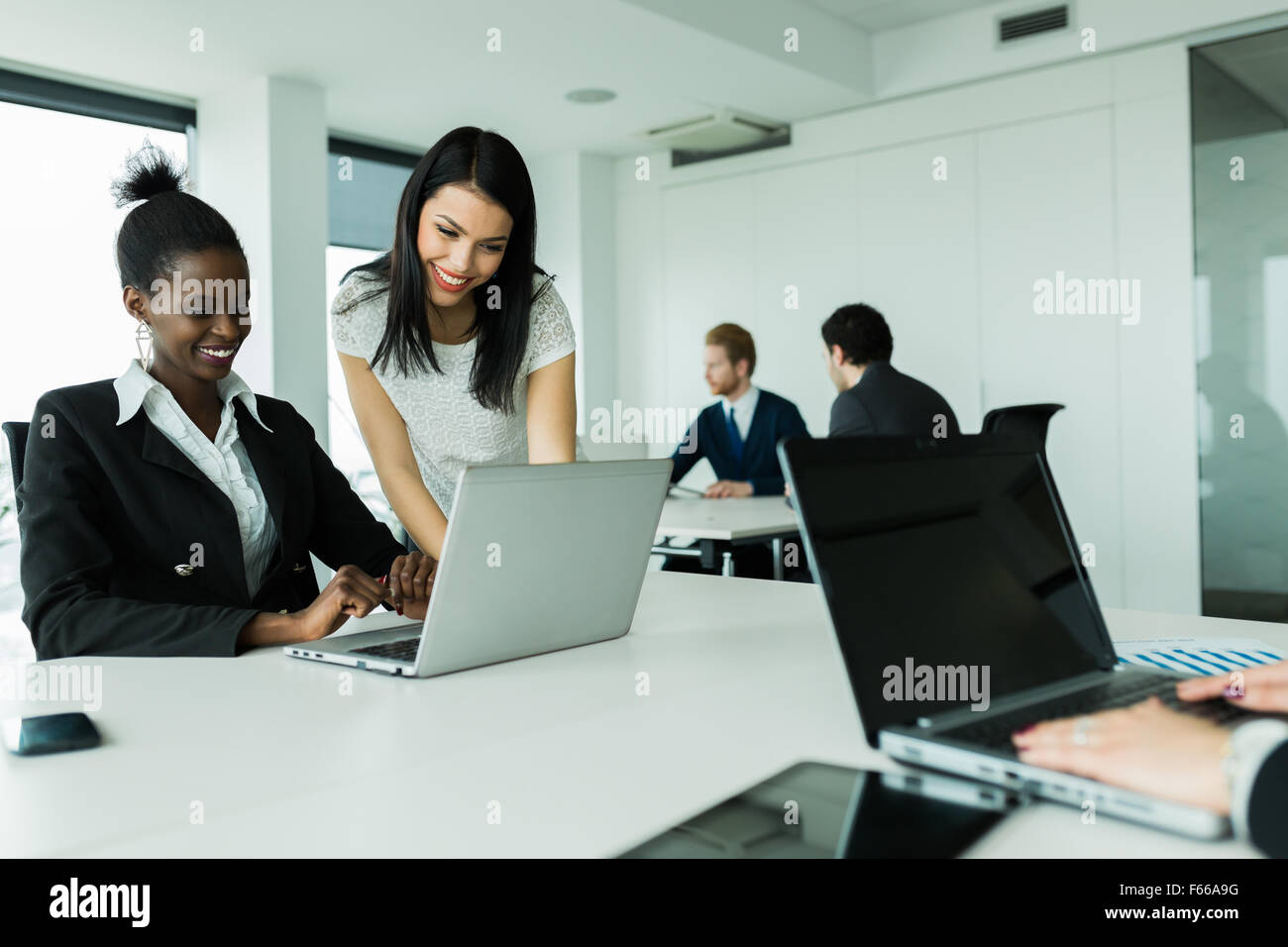 Black and white businesswomen looking at a laptop and working in a neat office environment - Stock Image