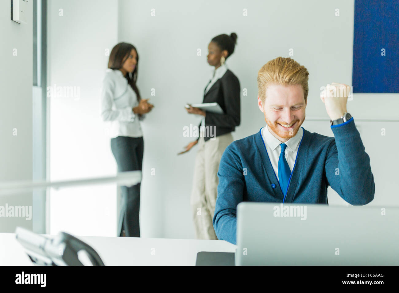 Successful businessman being happy for achieving his goals as he sees good news on the laptop - Stock Image