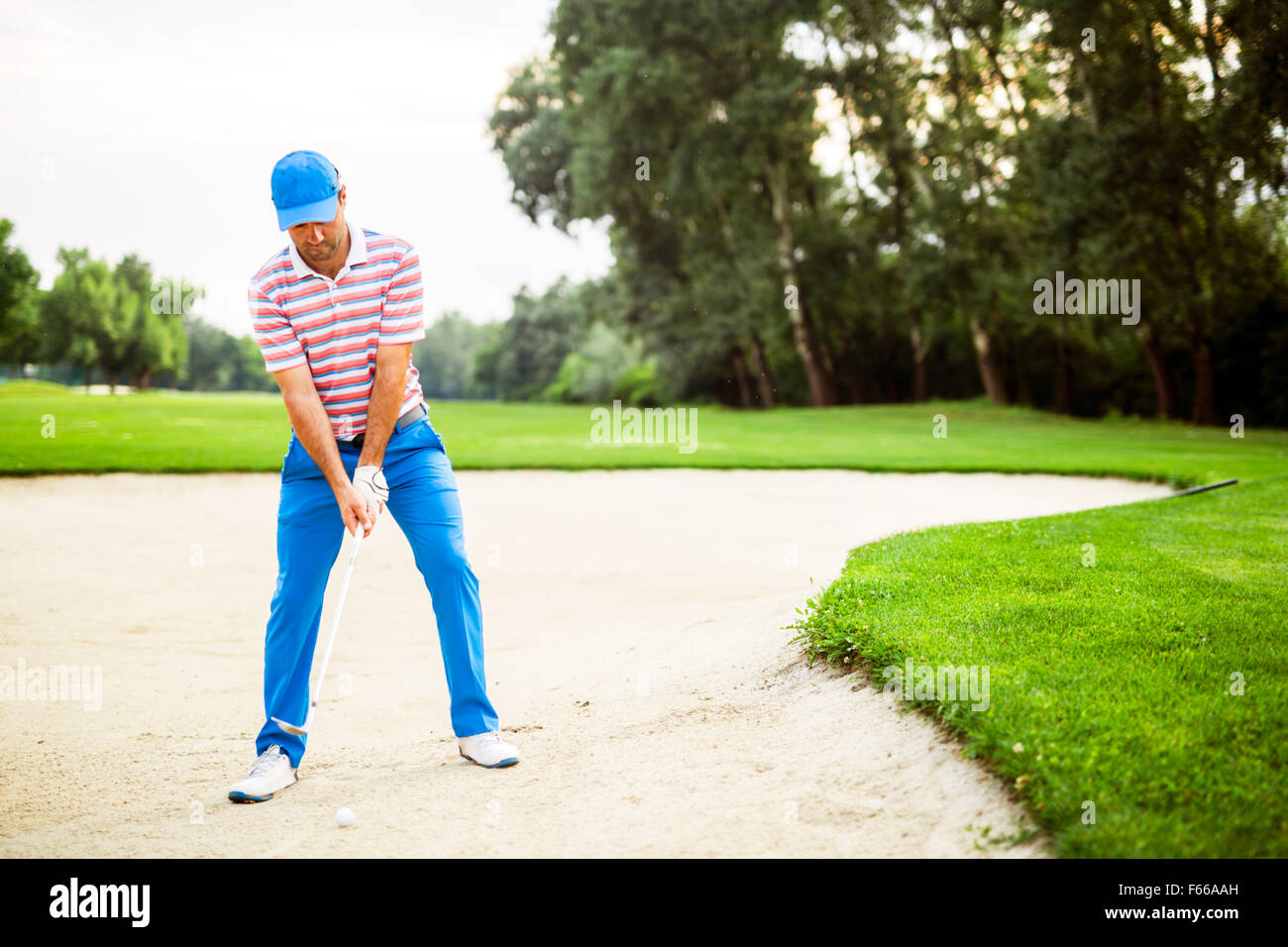 Golfer taking a bunker shot with the ball being in sand - Stock Image