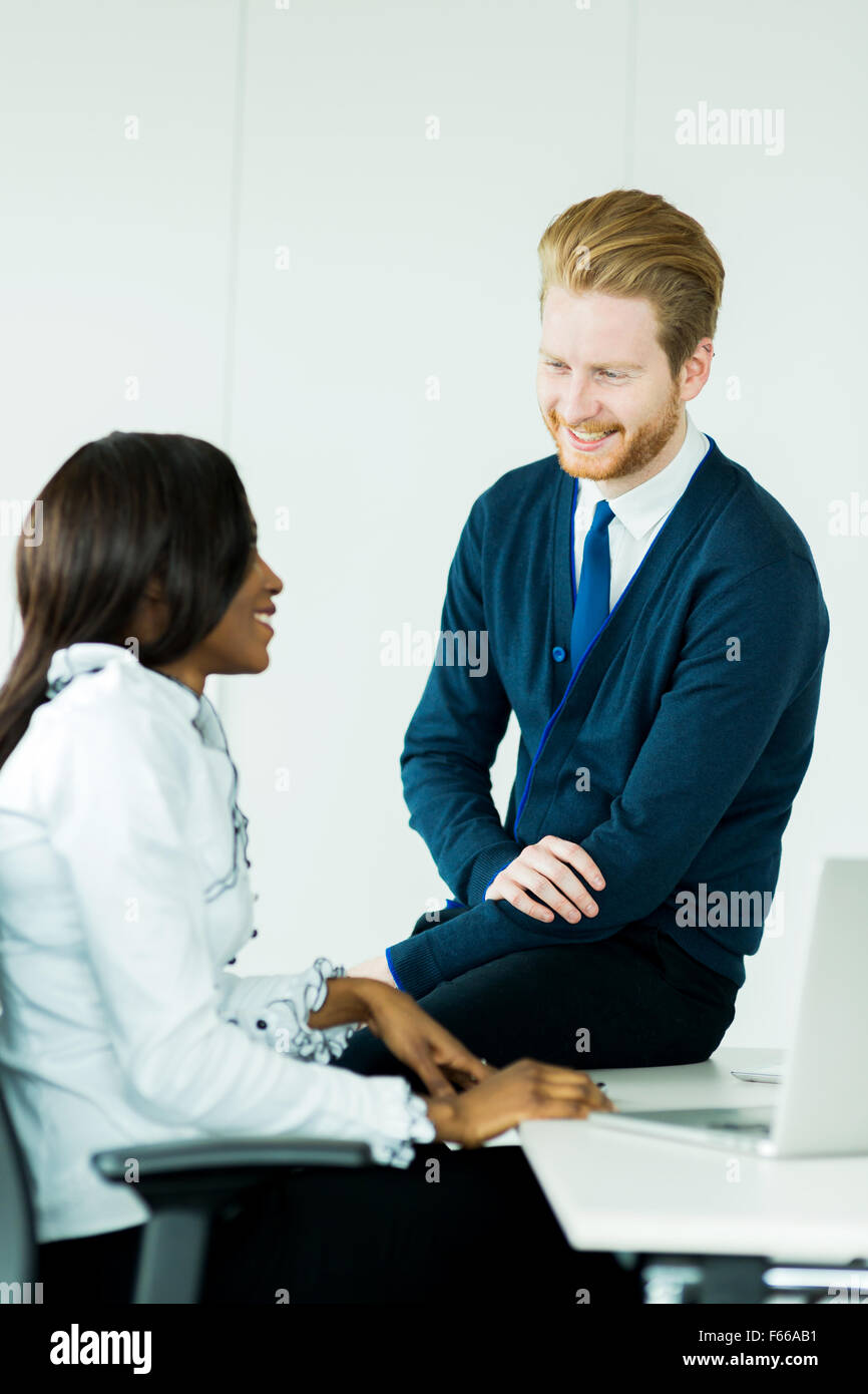 Exchange of thoughts during business meeting break as the businessman sits on the desk - Stock Image