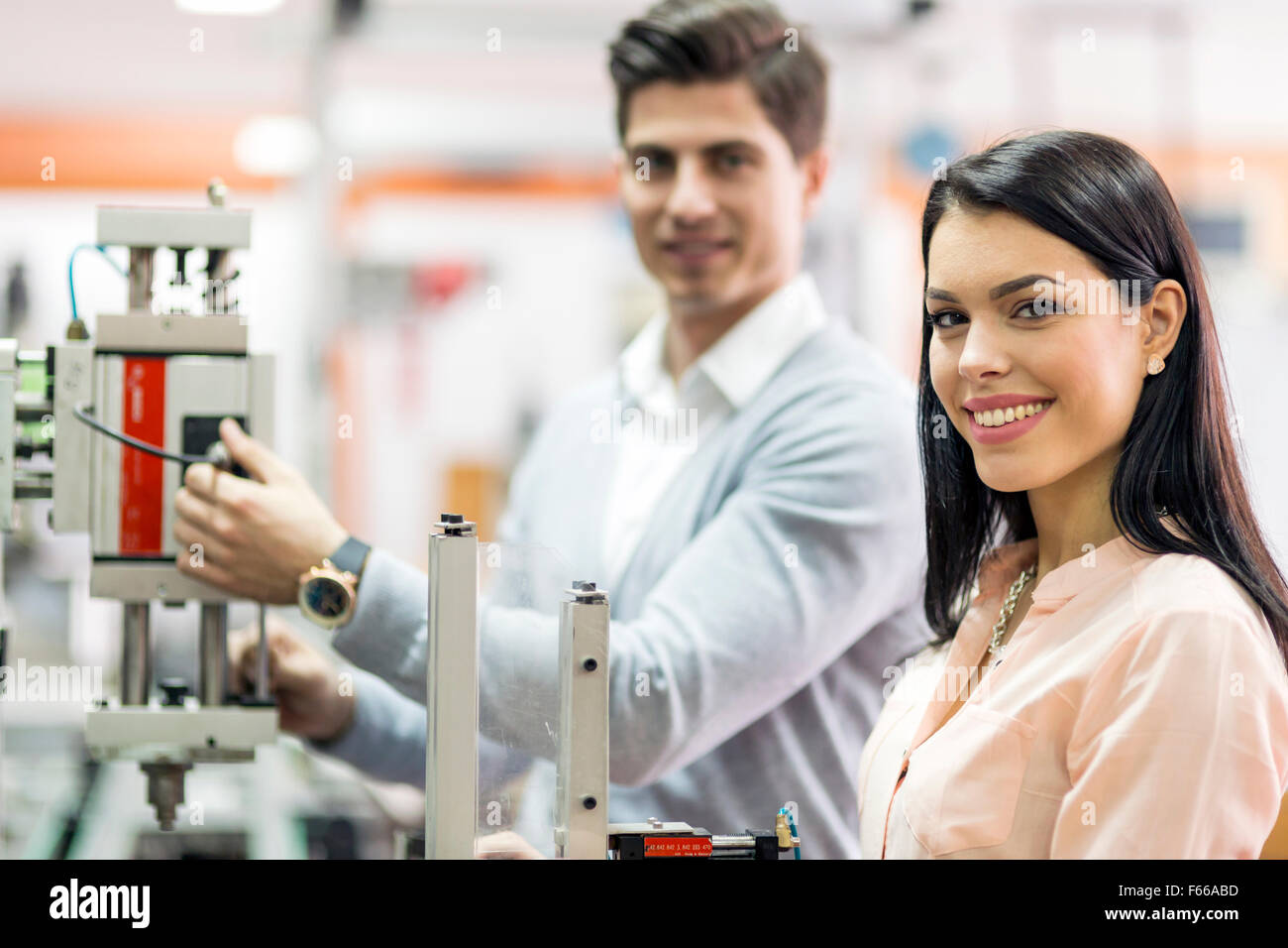 Two young students working on a science project together in lab - Stock Image